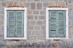 Två gamla fönster med stängda slutare på ett gammalt hus Arkivbilder