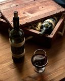Två gamla flaskor av rött vin i tappningspjällåda bland trä som rakar på träbakgrund och en kopp, utvald fokus royaltyfri fotografi