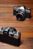 Två gamla kameror på träbakgrund Fotografering för Bildbyråer