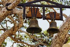 Två gamla kyrkliga klockor som hänger på territoriet av den Preveli kloster Arkivfoto