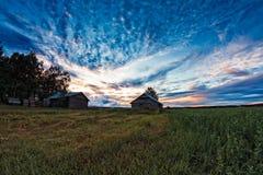 Två gamla ladugårdhus i solnedgången för sen sommar Arkivbilder