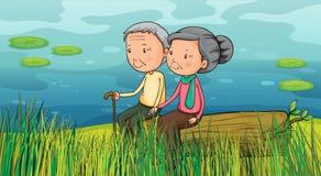 Två gamla människor som sitter nära sjön Arkivbilder