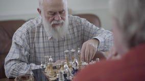 Två gamla människor som spelar en lek av schack som hemma sitter på lädersoffan Skäggig man som gör en flyttning Caucasian gamala stock video