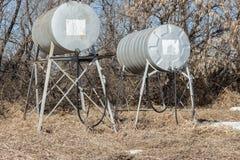 Två gamla runda metallbränsle- och gasbehållare med slangen och dysan Arkivfoto