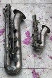 Två gamla saxofoner på stentegelplattagolv med blommakronblad Royaltyfri Fotografi