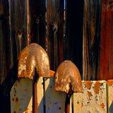 Två gamla skyfflar som lutar på ett staket Royaltyfria Bilder
