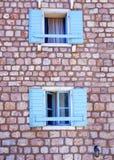 Två gamla träblåa fönster på väggen av huset arkivbilder