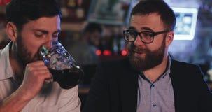 Två gamla vänner som dricker utkastöl och talar i sportstången Vänner som sitter på stångräknaren som dricker öl och lager videofilmer