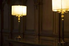 Två gammalmodiga lampor på ett skrivbord i ett trä paneled rum royaltyfri bild