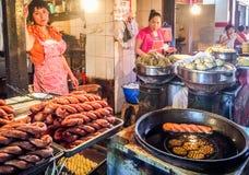Två gatasäljare säljer kinesisk traditionell mat i en öppen marknad i Kina Royaltyfri Bild