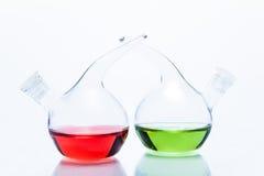 Två genomskinliga glass droppglassflaskor med färgflytande Arkivbilder