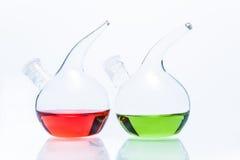 Två genomskinliga glass droppglassflaskor med färgflytande Royaltyfria Bilder