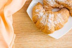 Två giffel i pudrat socker på en vit platta på en trätabell royaltyfri fotografi
