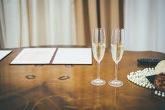 Två gifta sig champagneexponeringsglas på den träbruna tabellen arkivfoton