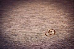 Två gifta sig guld- cirklar på bakgrund Arkivfoto