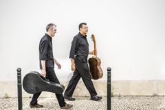 Två gitarrister som går med deras instrument på gatan royaltyfri foto