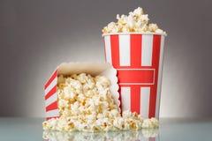 Två gjorde randig askar av popcorn och spillt popcorn på grå färger royaltyfri fotografi