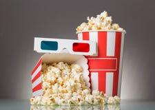 Två gjorde randig popcornaskar, exponeringsglas 3D och popcorn som spilldes på gra royaltyfria foton