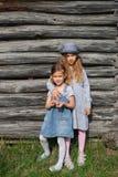 Två glade systerflickor i blå tillfällig kläder som poserar vid en trävägg aktiv livsstil Ungdommode royaltyfri foto