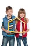 Barn är hållande modellerar av ett hus Royaltyfri Foto