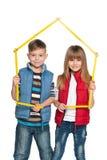 Två barn är hållande modellerar av ett hus Arkivbild
