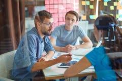 Två gladlynta affärsmän som talar om affär medan en av dem som pekar datorbildskärmen Royaltyfri Bild