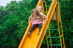 Två gladlynta barn rullar ner den gula glidbanan på lekplatsen och skri på en spännande hastighet royaltyfri foto
