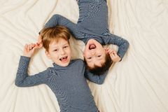 Två gladlynta bröder ligger på en vitt filt och skri Royaltyfri Bild