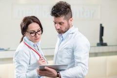 Två gladlynta doktorer som använder en digital minnestavla Royaltyfria Foton
