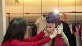 Två gladlynta flickor försöker på hattar i en innegrej shoppar och skrattet Shoppa på plats arkivfilmer