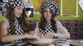 Två gladlynta flickor i likformig som lagar mat en pizza på mästarklass i kafét 4K stock video