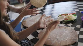 Två gladlynta flickor i likformig som lagar mat en pizza på mästarklass i kafét 4K lager videofilmer