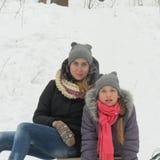 Två gladlynta flickor sitter i snön Arkivfoto