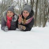 Två gladlynta flickor sitter i snön Fotografering för Bildbyråer