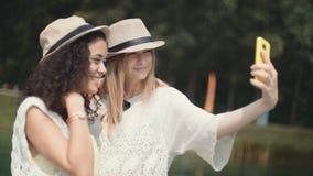 Två gladlynta flickor som gör selfies vid en sjö stock video
