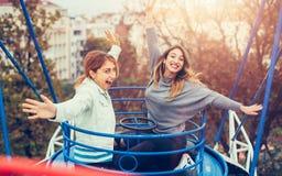 Två gladlynta flickor som har gyckel på glat, går rundan arkivfoto