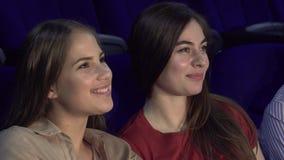 Två gladlynta flickvänner som viskar, medan hålla ögonen på en film fotografering för bildbyråer