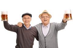 Två gladlynta pensionärer som rymmer halva liter av öl Royaltyfria Bilder