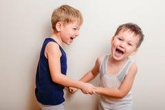 Två gladlynta pojkar spelar tillsammans och skriker arkivfoto