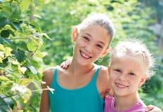 Två gladlynta systrar som spelar i parkera i varm sommardag fotografering för bildbyråer