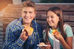 Två gladlynta tonåringar, flicka och pojke som äter pizza Arkivbild