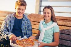Två gladlynta tonåringar, flicka och pojke som äter utomhus- pizza Royaltyfria Bilder