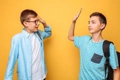 Två gladlynta tonåringar, grabbar hälsar sig, på en gul bakgrund royaltyfri foto