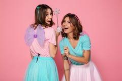Två gladlynta unga flickor som kläs som feer med vingar Fotografering för Bildbyråer