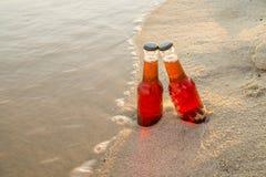 Två glasflaskor av körsbärsrött öl på sanden med flödande vatten lite varstans Royaltyfria Bilder