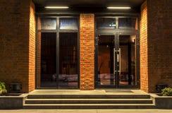 Två glass dörrar i en tegelstenbyggnad i natten royaltyfri bild