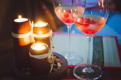 Två glass exponeringsglas med champagne och tända stearinljus Aftonromantikeratmosfär royaltyfri bild