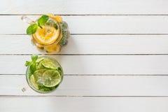Två glass exponeringsglas med hemlagad lemonad från limefrukt och citronen på en vit trälantlig bakgrund Royaltyfri Bild