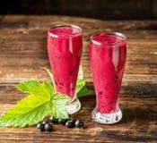 Två glass exponeringsglas med smoothien för svart vinbär Arkivfoton
