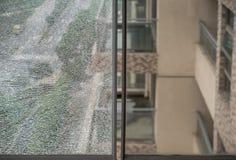 Två glass fönster med ett som är brutet, & ett som är intakt arkivbild